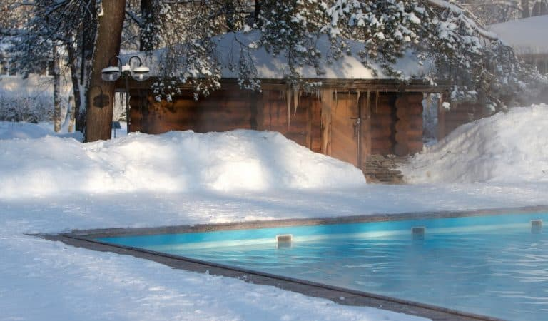 Warm swimming pool with blue water and wooden Russian bath in sunny winter weather, outdoor.