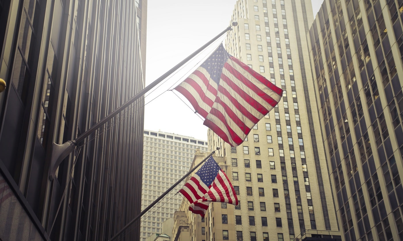 A shot of two American or US flags on a high rise building