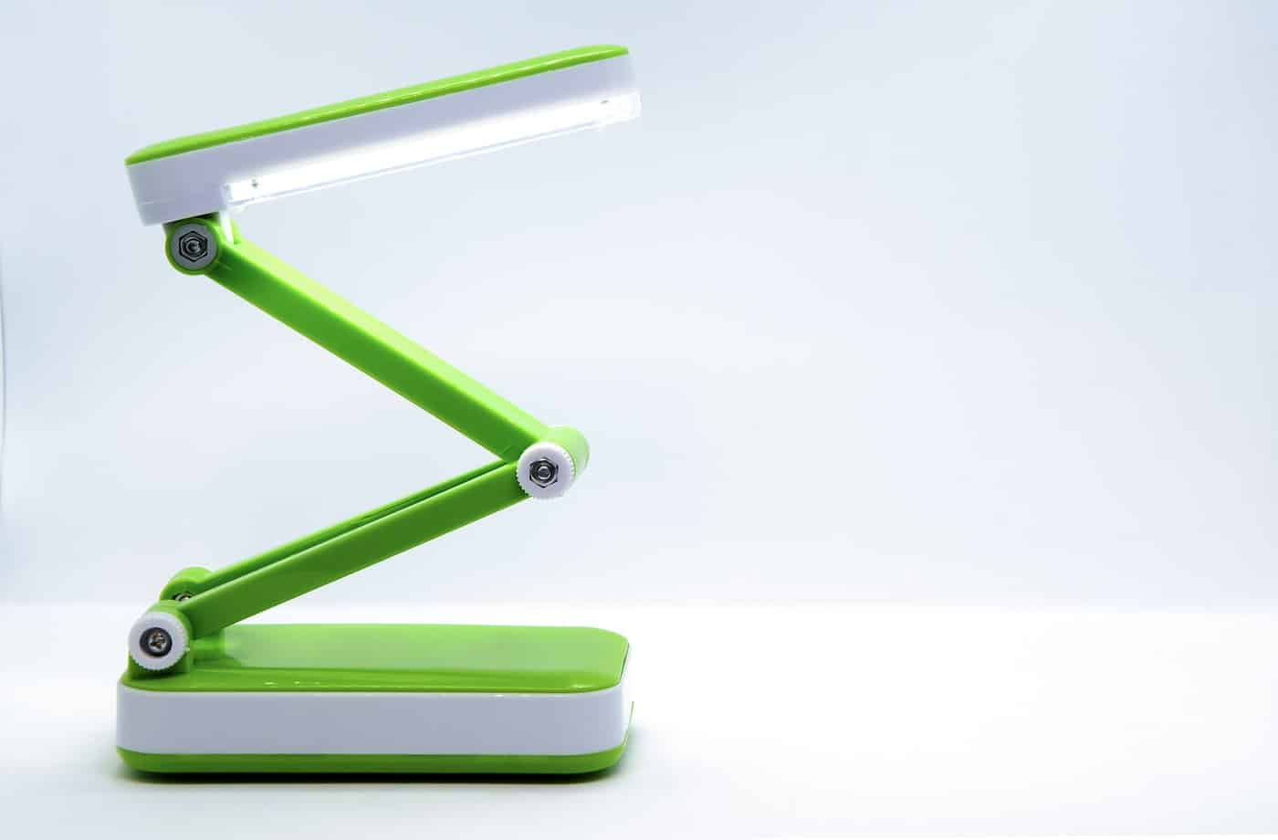 Compact foldable portable LED Desk Lamp with flexible body made of bright green plastic on a white background. Space for text.