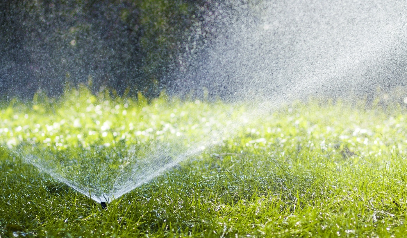 Lawn water sprinkler spraying water over grass in garden on a hot summer day. Automatic watering lawns. Gardening and environment concept.
