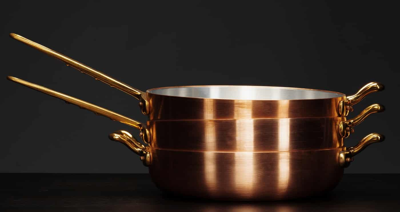 Set of copper cookware over dark background