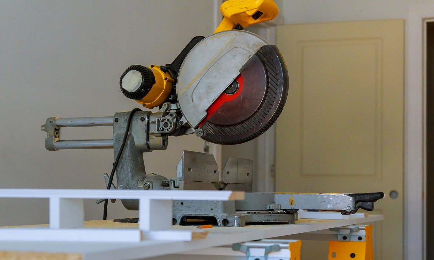 contractor uses a circular saw to cut trim molding Miter Saw on a construction site with a worker in background