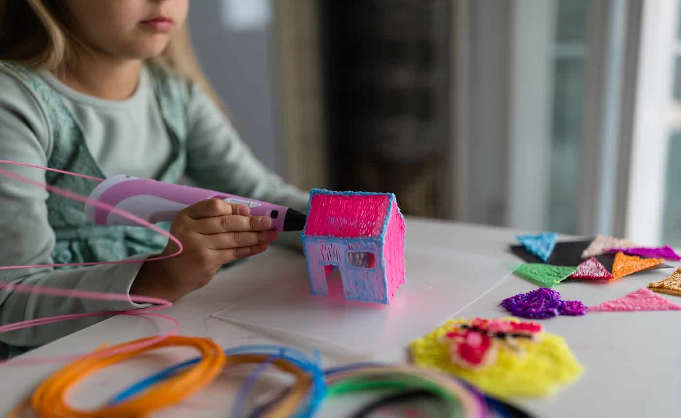 Cute little girl with blonde hair makes a plastic house, draws parts with a 3D pen. STEM and STEAM education. Development, modeling, education, design with hot plastic. Modern technologies. DIY.