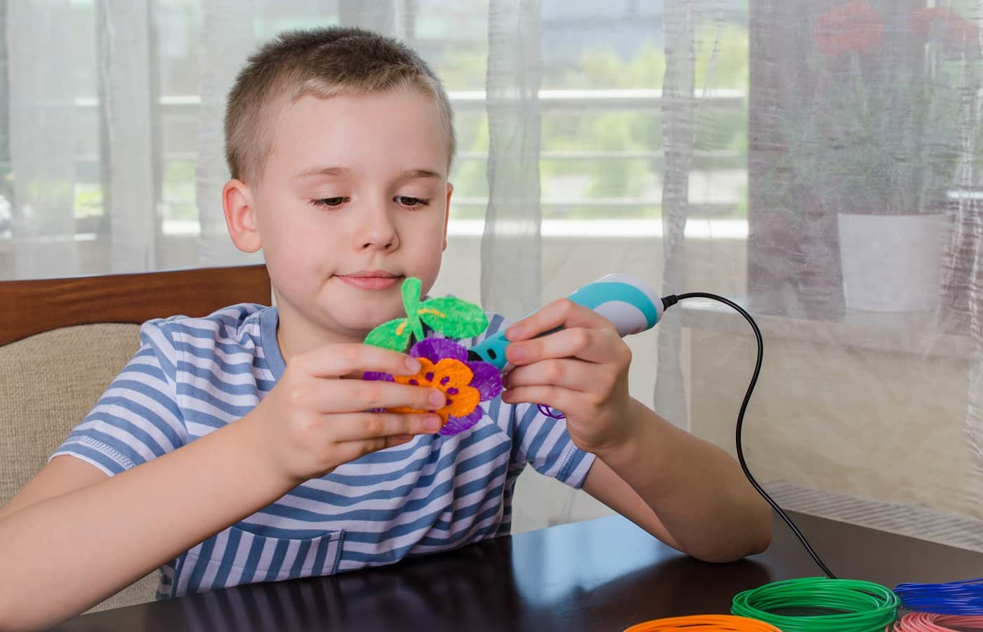 Boy using 3D pen. Happy child making flower from colored ABS plastic. Creative hobby at home, technology, leisure, education concept.