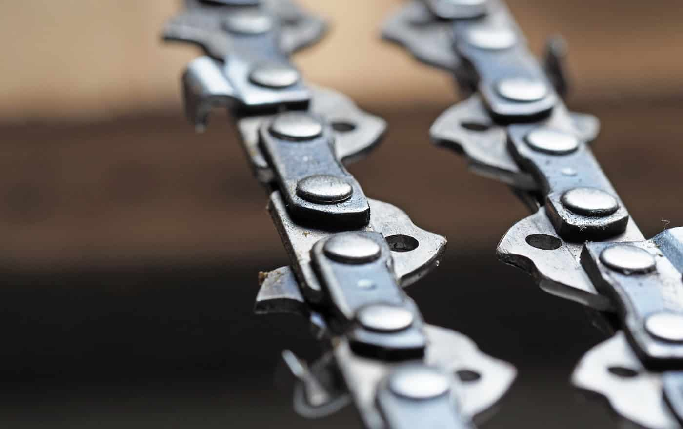 metal chainsaw chain with sharp teeth close-up with blurred background