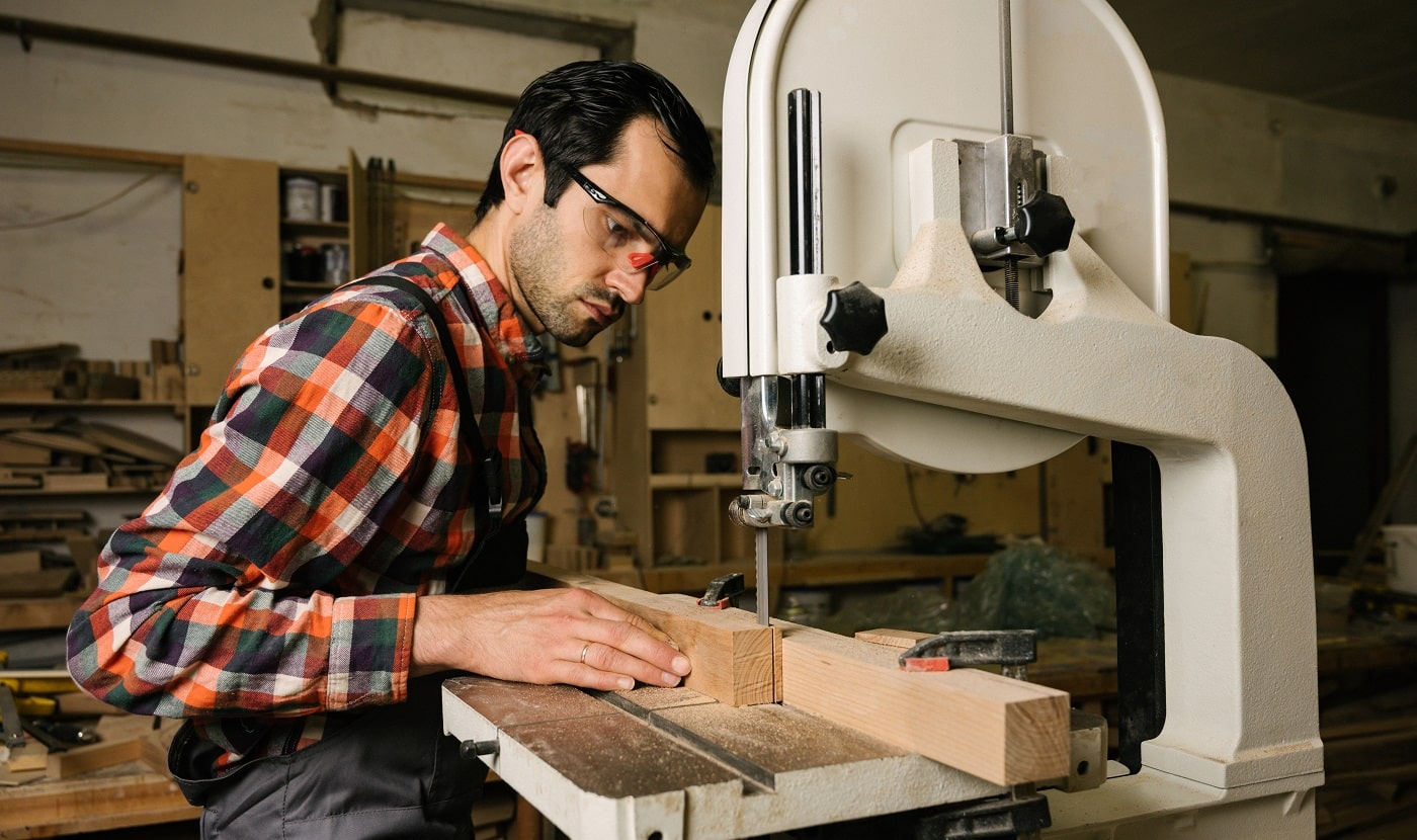 Working process in the carpentry workshop.A man in overalls works on a band saw in a carpentry workshop.Profession, carpentry, woodwork and people concept