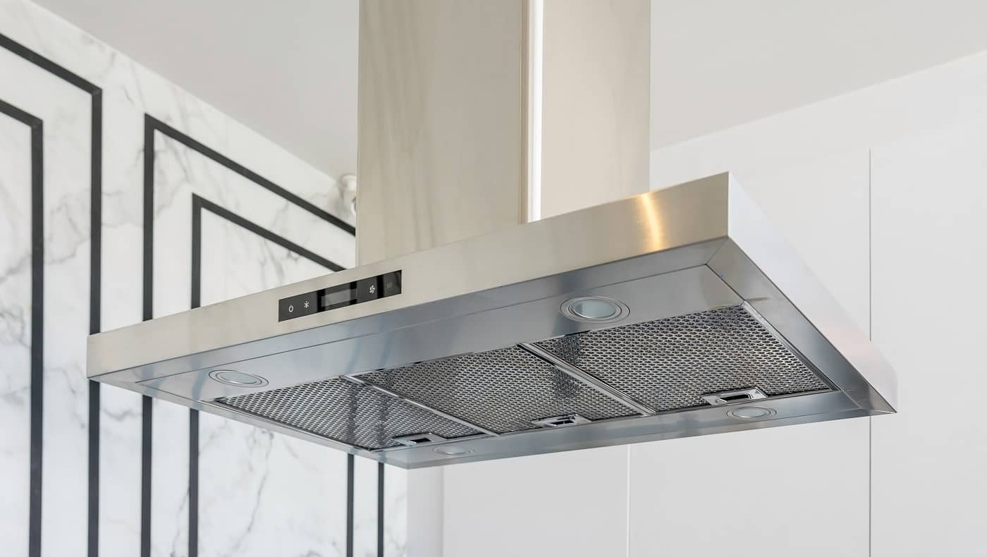 Modern stainless steel And Range hood in the kitchen interior. Stainless Steel Cooker Hood with light on. Kitchen Appliances