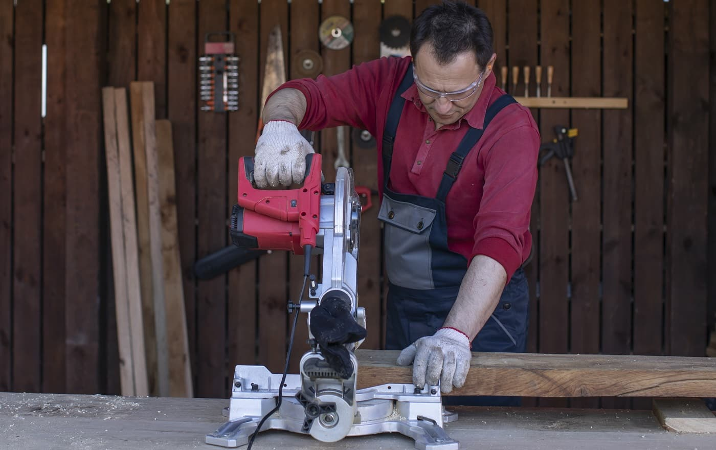 A man in protective overalls and glasses cuts a wooden beam using a circular saw. Home furniture workshop. Artisan works in his carpentry workshop.