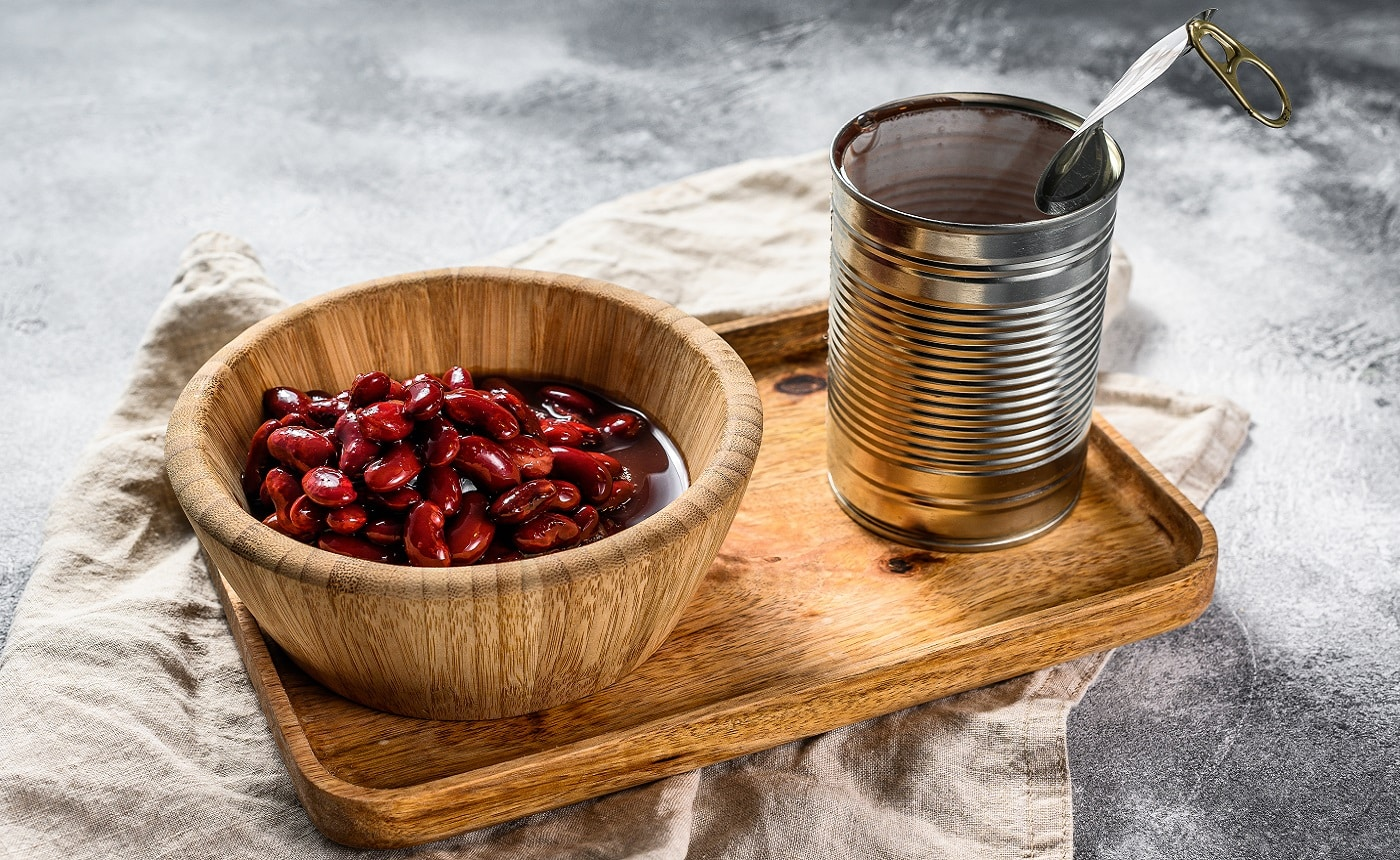 Red canned beans in an aluminum can. Gray background. Top view.