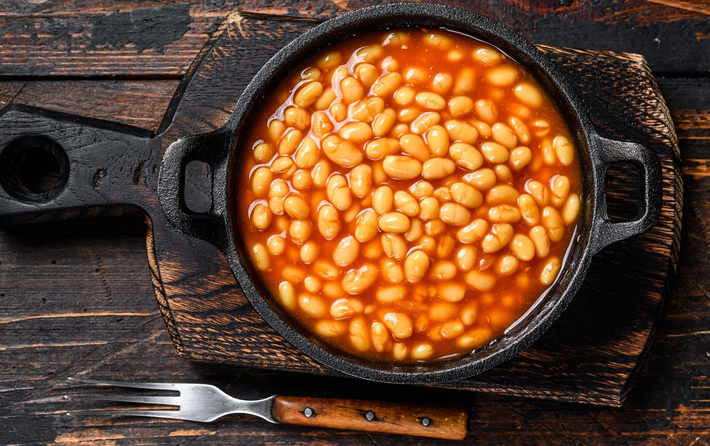 Beans in tomato sauce in a pan. Dark wooden background. top view.