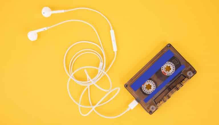 Tape cassette and white headphones. Composition in the form of a player on a yellow background.