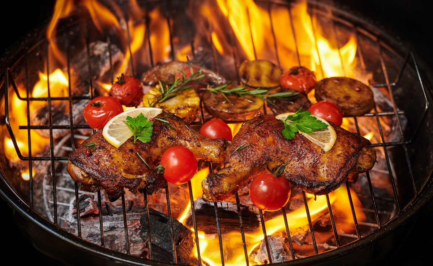 Grilled chicken legs on the flaming grill with grilled vegetables with tomatoes, potatoes, pepper seeds, salt. top view with copy space. tasty snack. flat lay. healthy lunch menu. diet food.