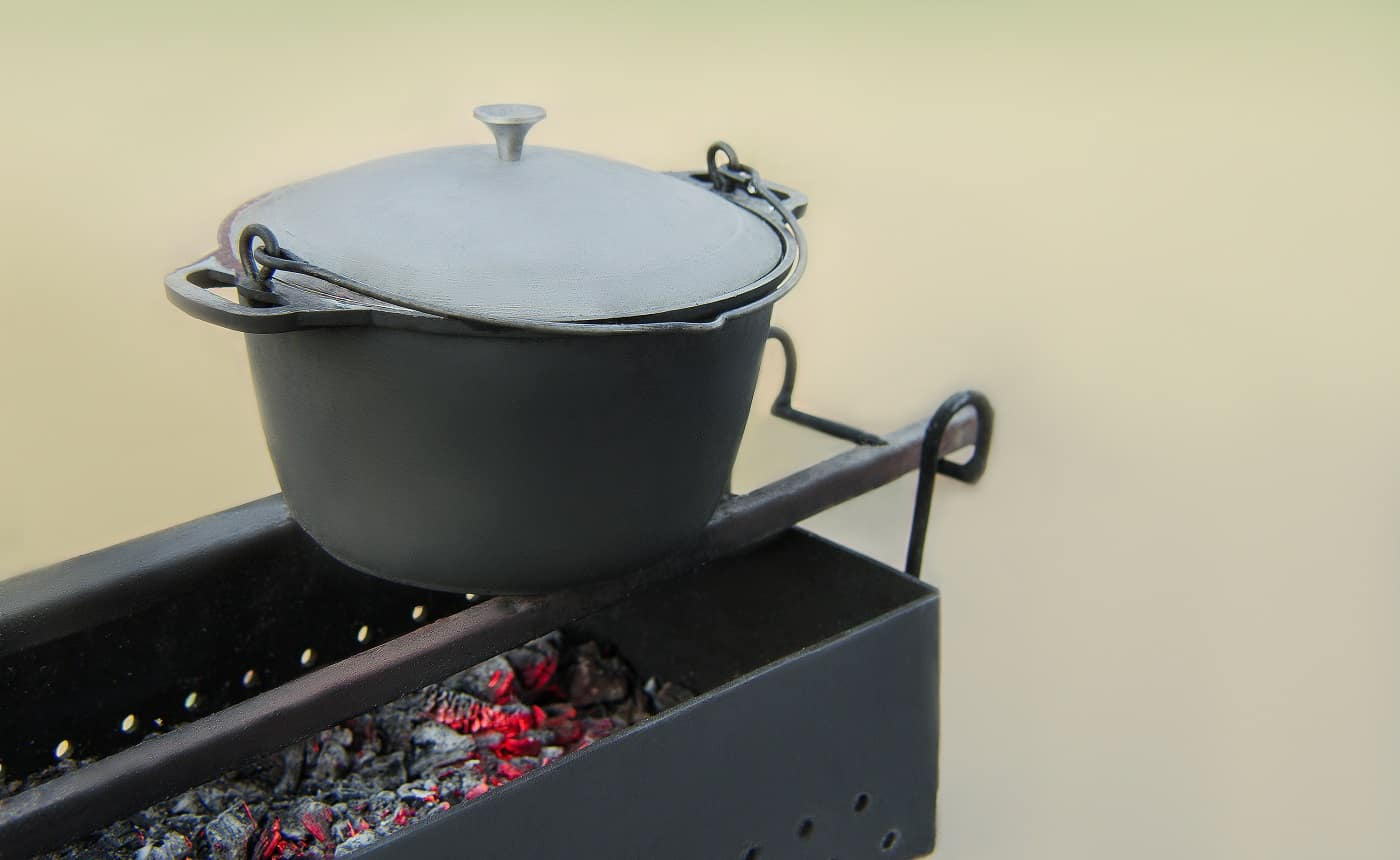 Old cast iron cauldron pan in soot on the grill with burning hot coals. Cooking in a nature