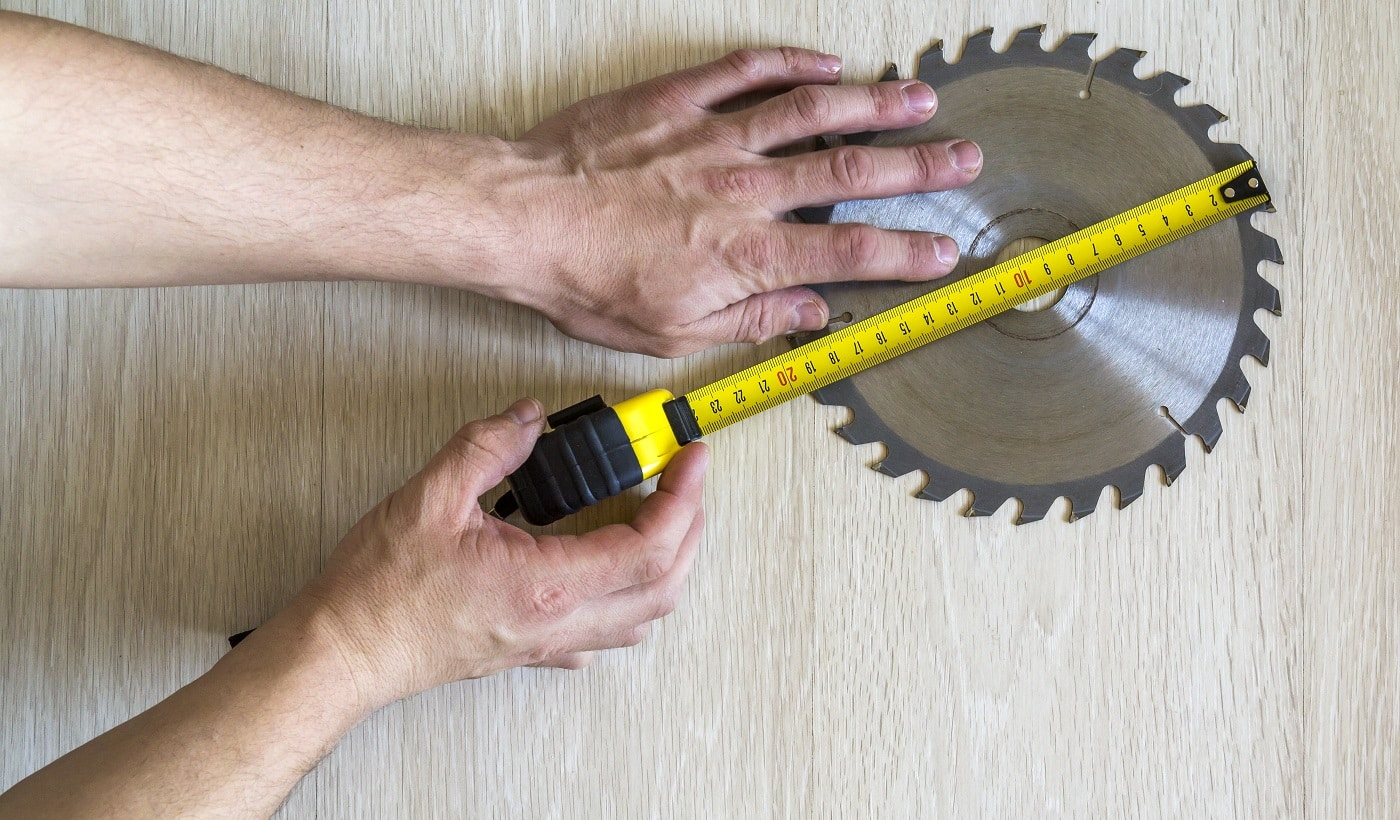 Close up of circular saw blade for wood work and worker hand with measuring tape on wooden background. Top view.