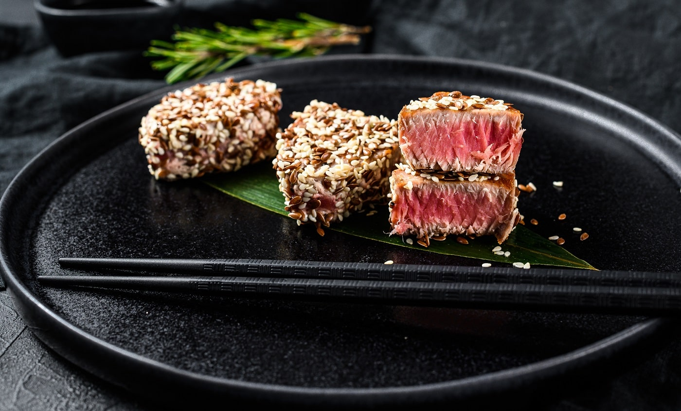 Grilled tuna steak on a plate. Black background. Top view.