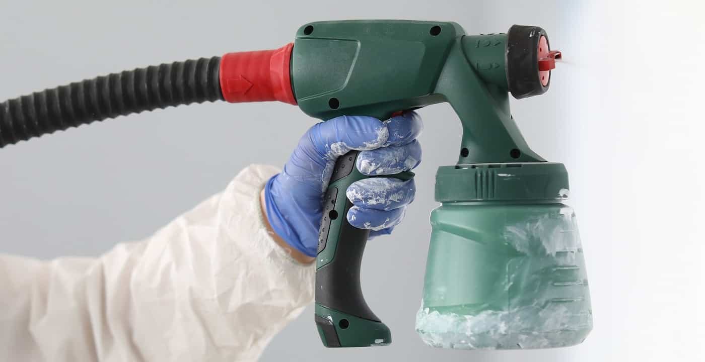 Master paint wall with white paint. Male hand in protective suit hold spray gun in his hand close up.