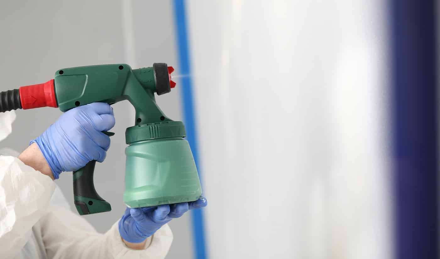 Closer-up of male person holding modern spray gun with paint. Qualified worker prepare for painting wall. Blue protective gloves. Empty space. Renovation and construction site concept