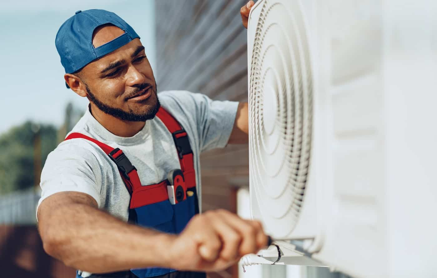 Young black man repairman checking an outside air conditioner unit close up