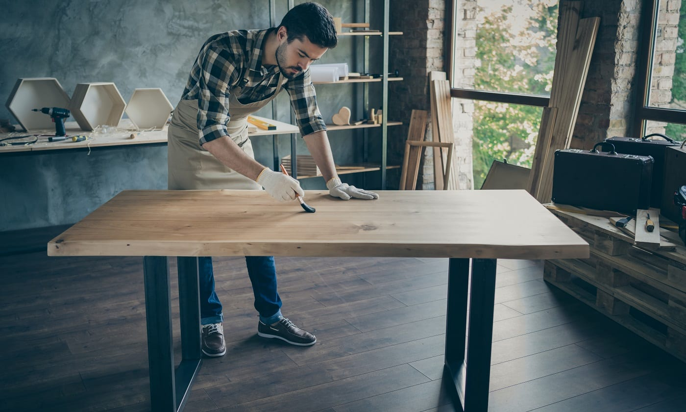 Full length photo of handsome careful guy covering handmade slab table oil varnish paint brush own wooden business industry woodwork shop garage indoors