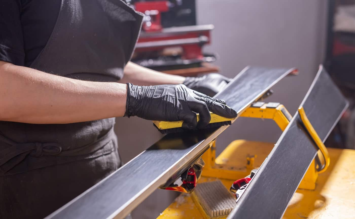 Work and repair concept - a man's hands repairing the ski by rubbing a paraffin.