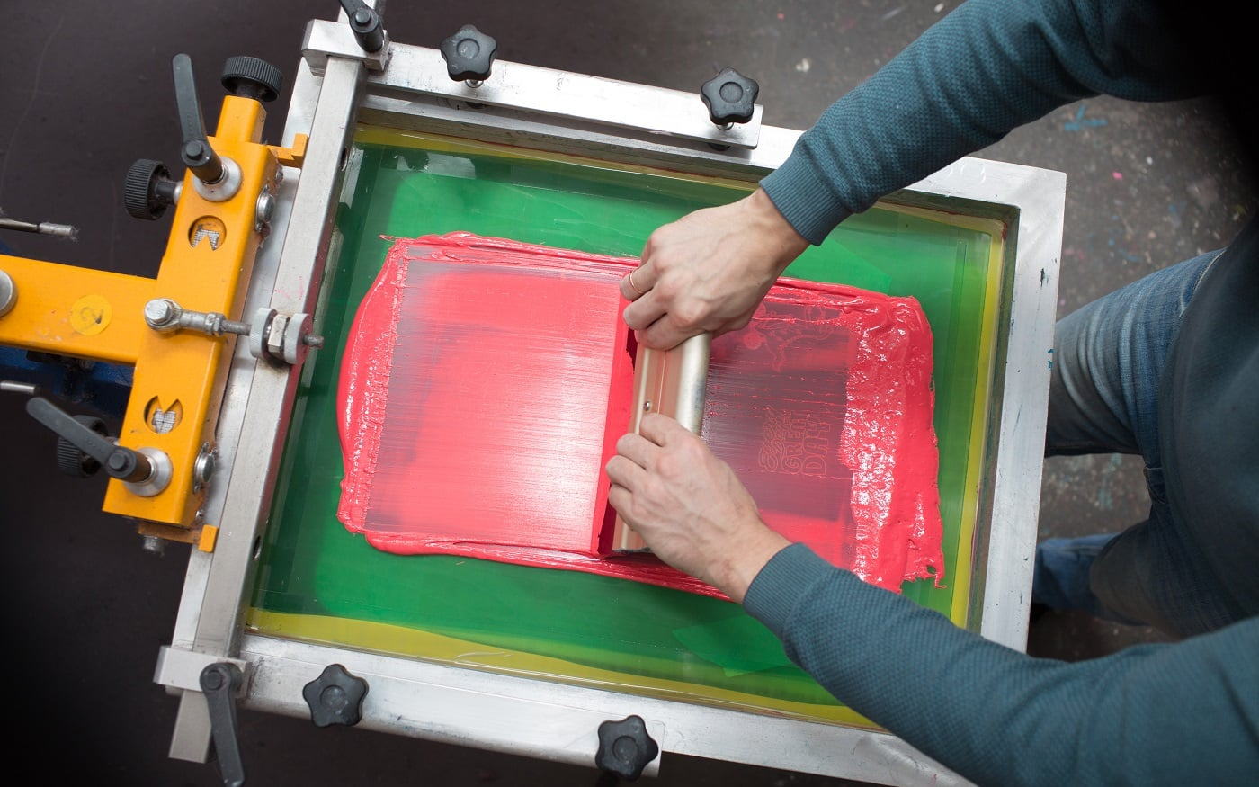 Silk screen printing. Serigraphy. Color paints and fabric. Plastisol paint and squeegee.