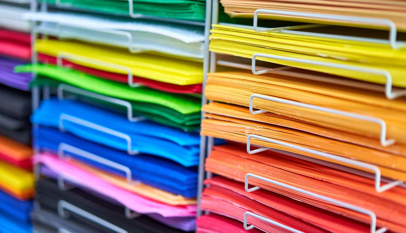 Sheets colored cardboard for designer creative works. Stacks multicolored drawing paper in the store. Colorful art papers on shelf for sale stationery store
