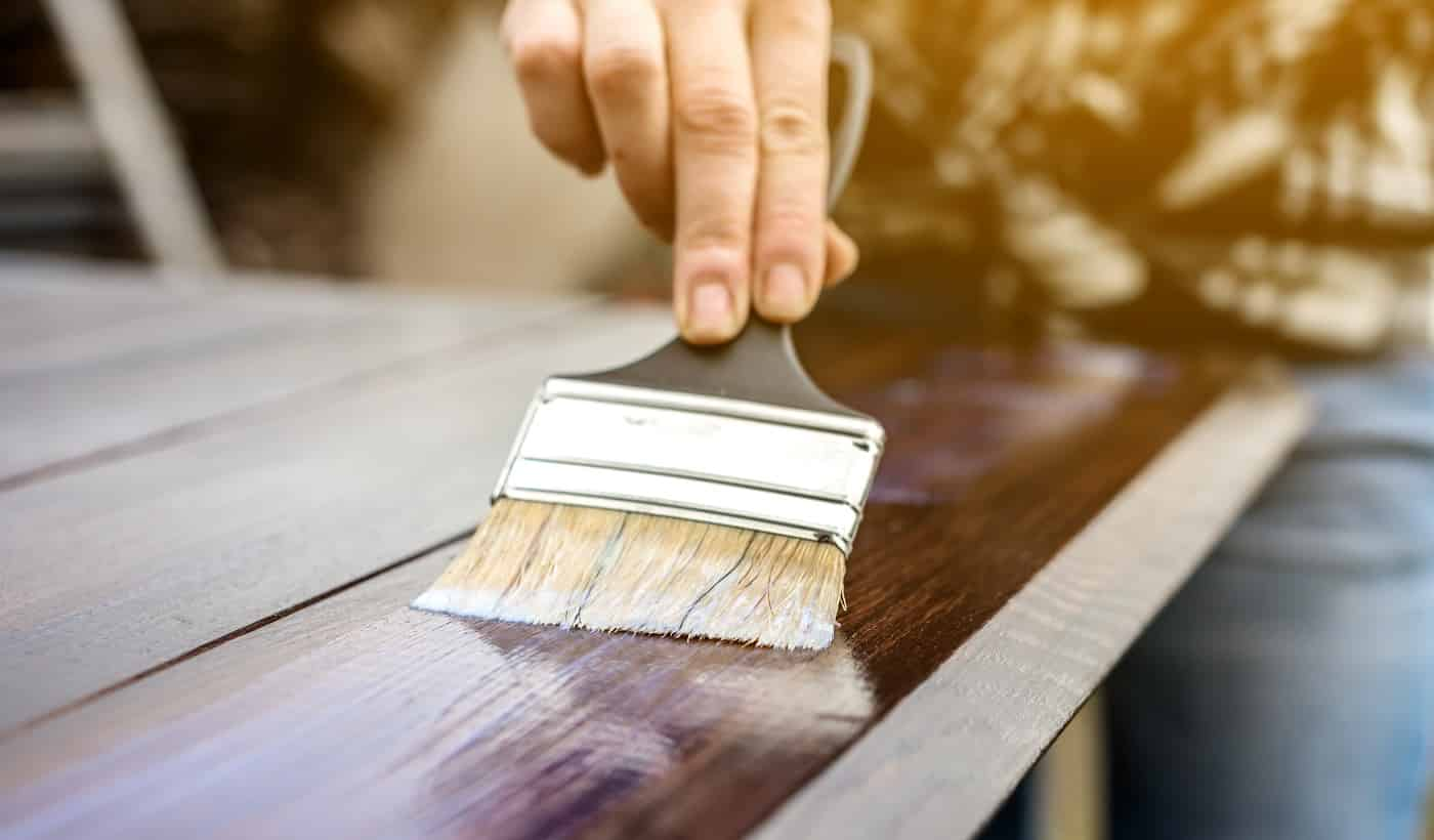 A wood carpenter applies a protective layer of transparent varnish. Hand with a brush close up on the table top
