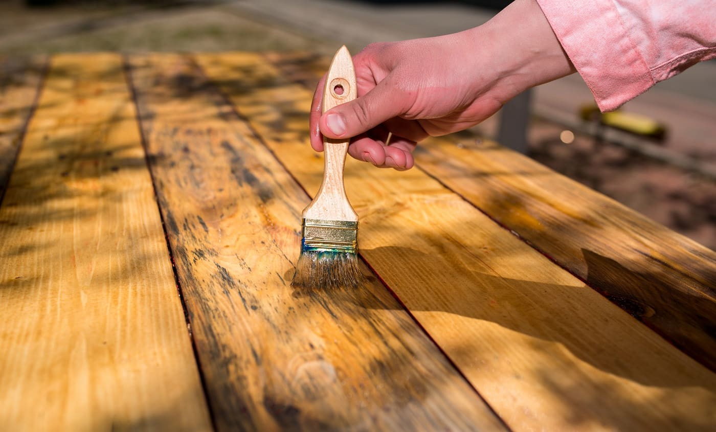 Hand with a brush varnishes wooden boards