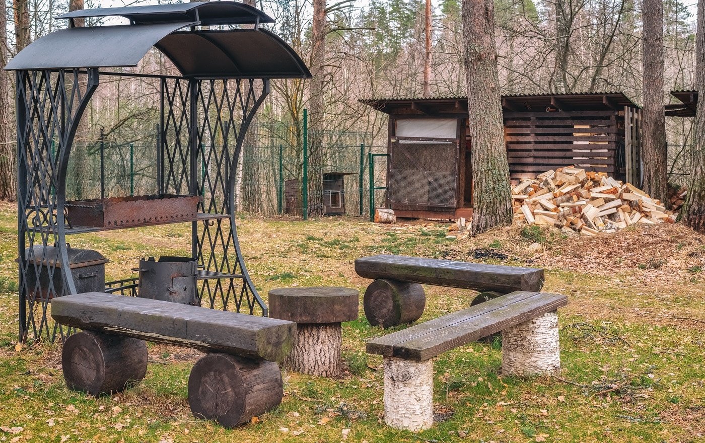Antique metal brazier made of wrought iron with a beautiful pattern on the background of wood and trees. Table and benches made of logs