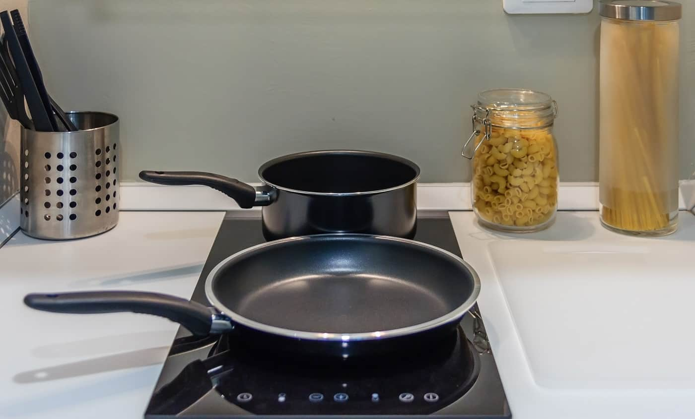 Black pan on Induction stove top panel in modern kitchen for cooking, closeup