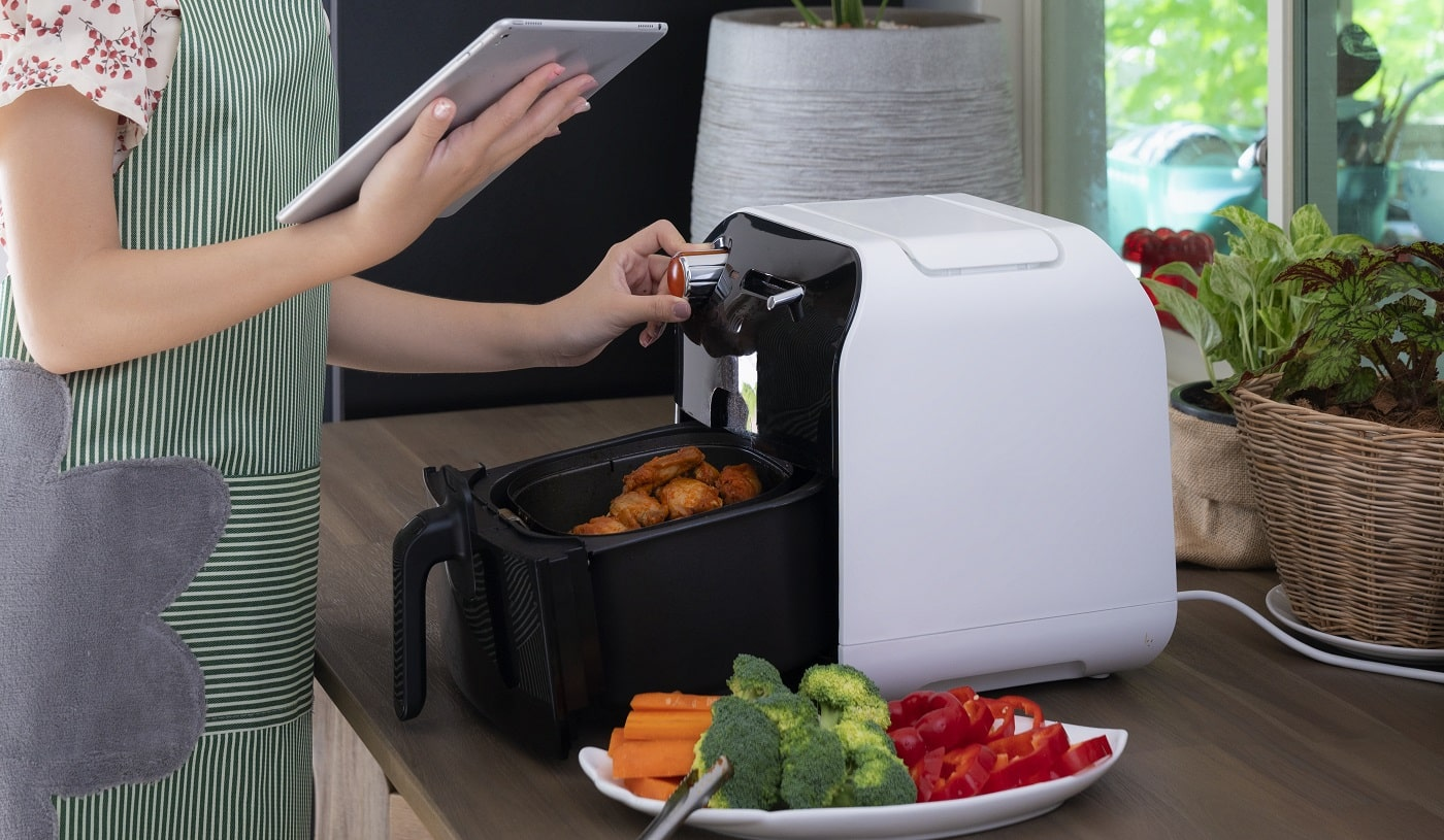 Asian wife made Oilless Air Fryer machine for cooking a fried chicken for today diner, this image can use for food, kitchen and technology concept.