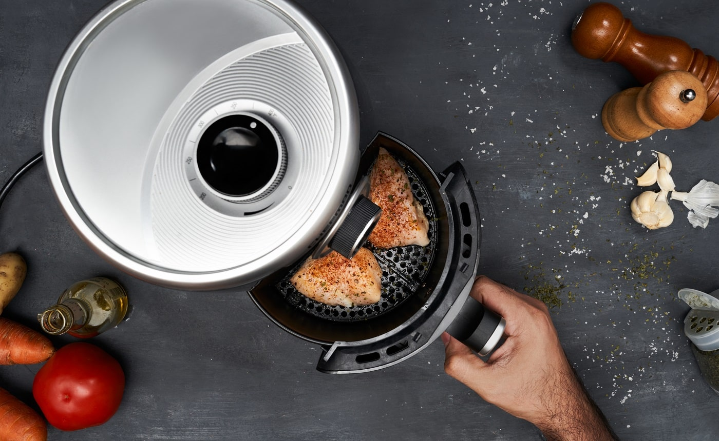Unrecognizable man hand cooking skinless chicken breast with spices in an air fryer