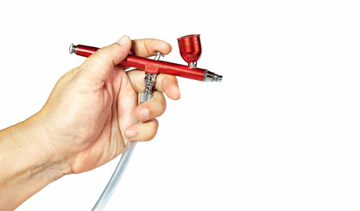 Red airbrush spray tool in hand for paintingg hobby or work for art .