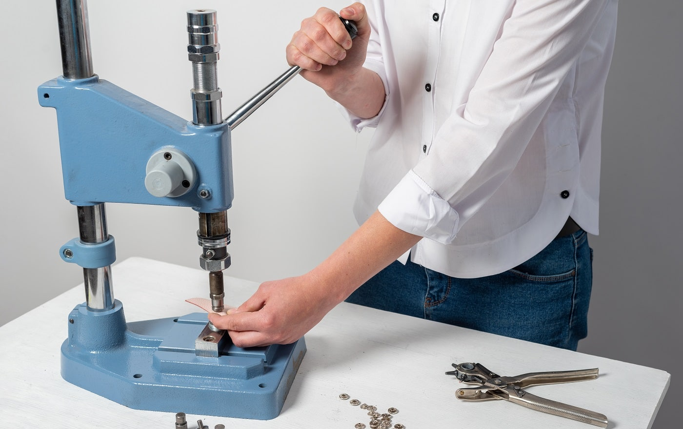 the hands of the master make holes for the buttons on a special installation press