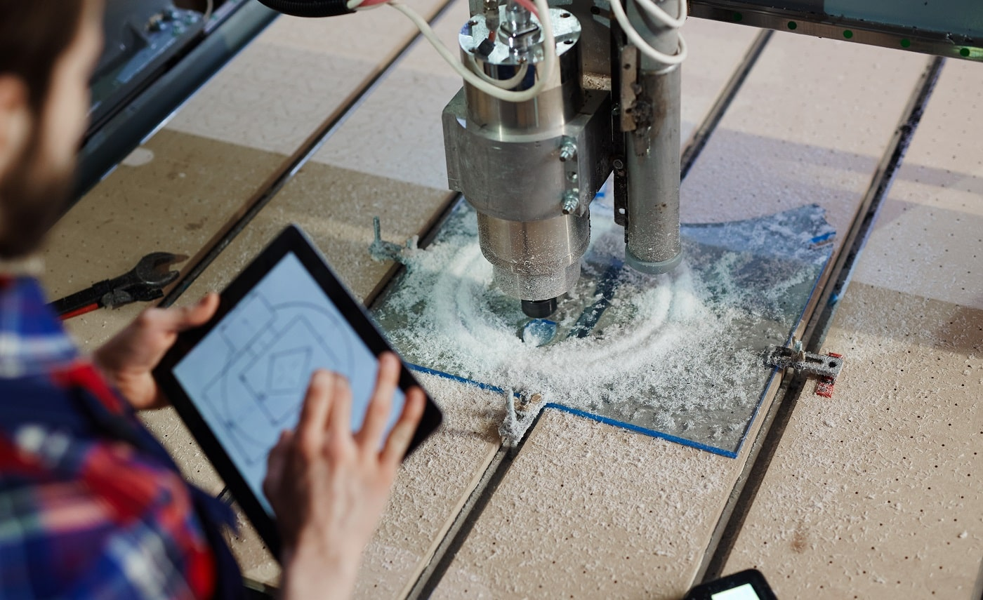 Engineer with touchpad and lathe machine
