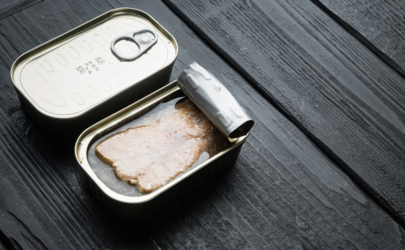 Canned Wild Alaska Salmon set, in tin can, on black wooden table background, with copyspace and space for text