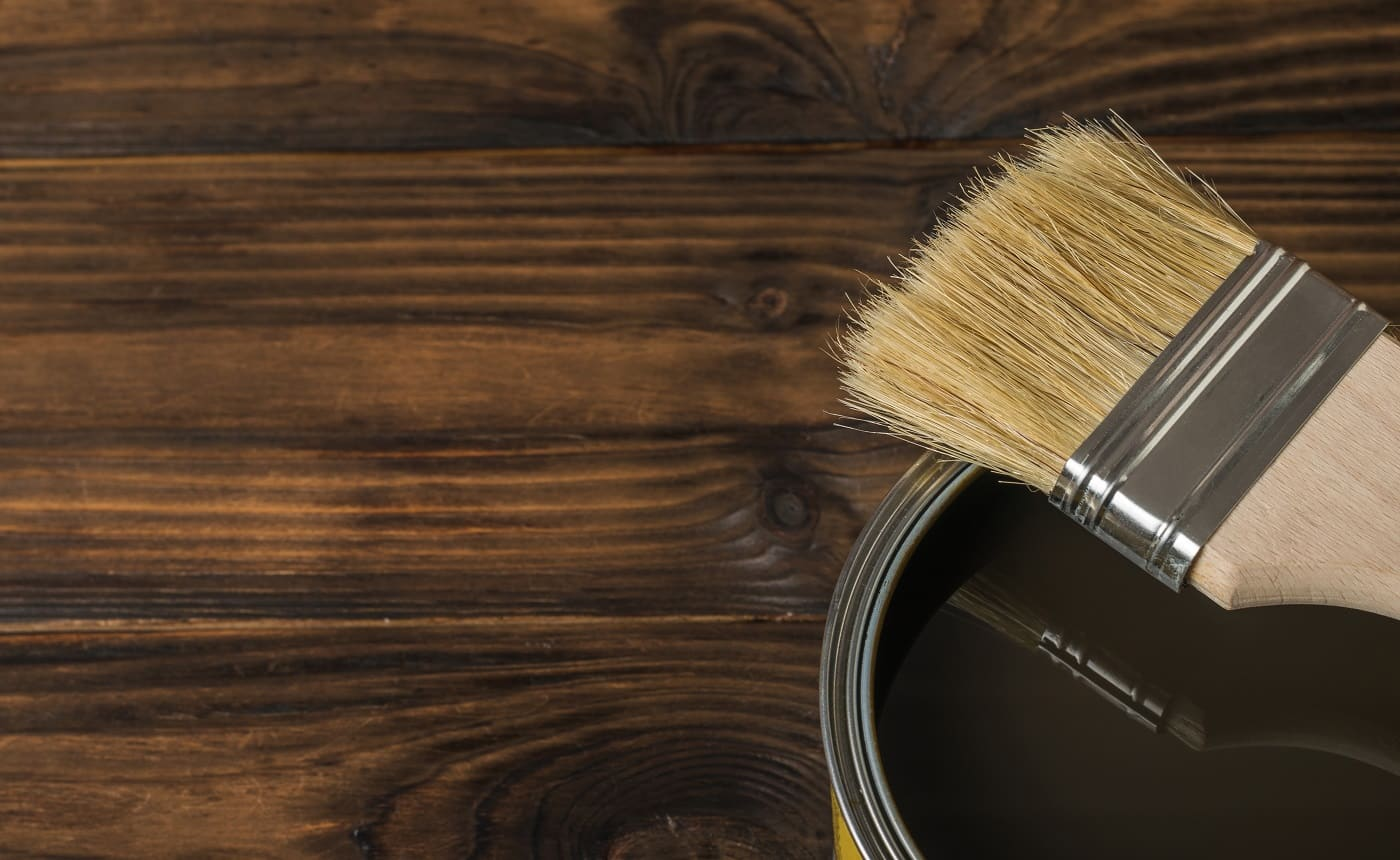 Brush on a tin with tinting composition on a wooden background. The rendering of wood.