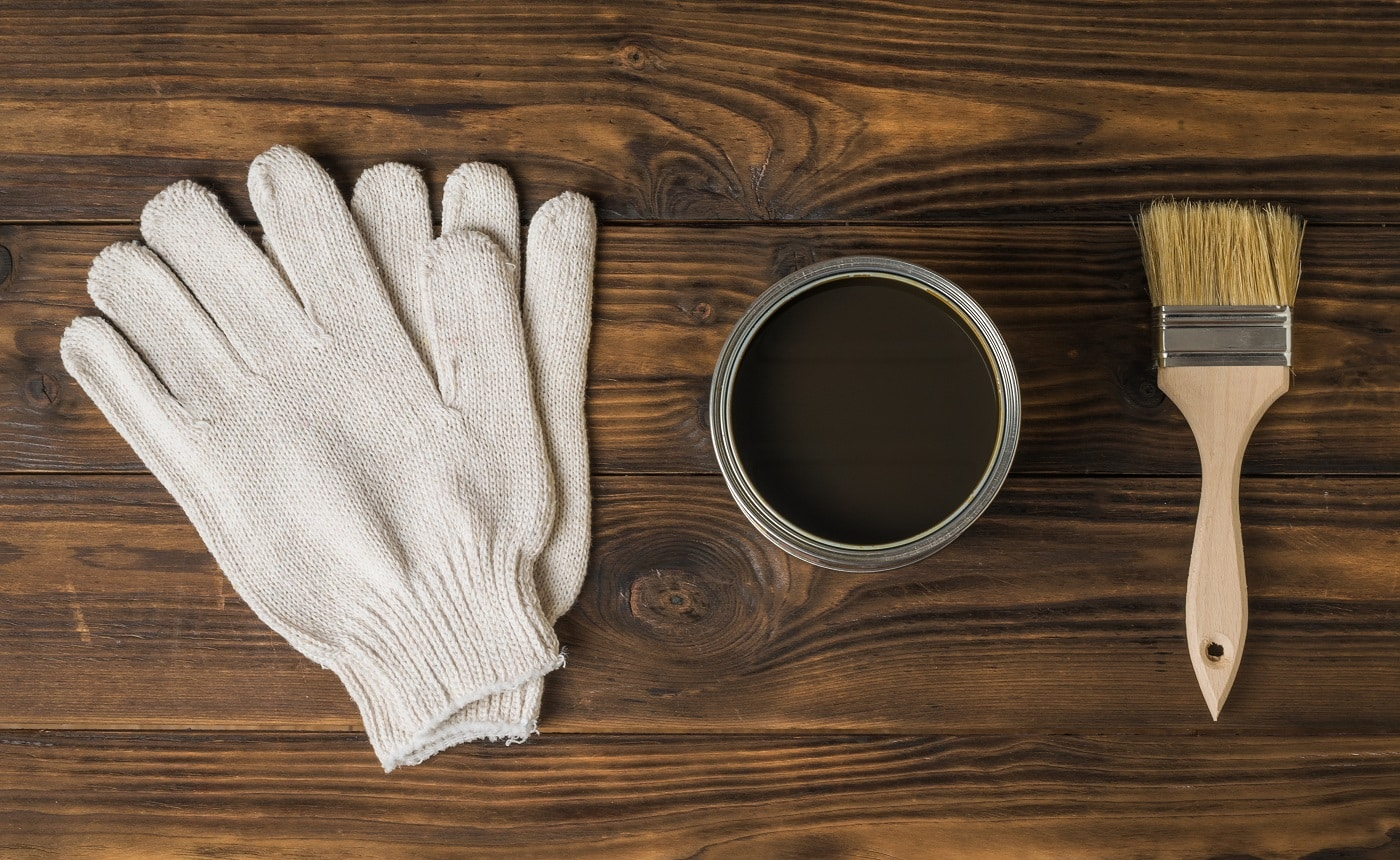 Brush, gloves and jar with a protective coating for wood on a wooden background. The rendering of wood.