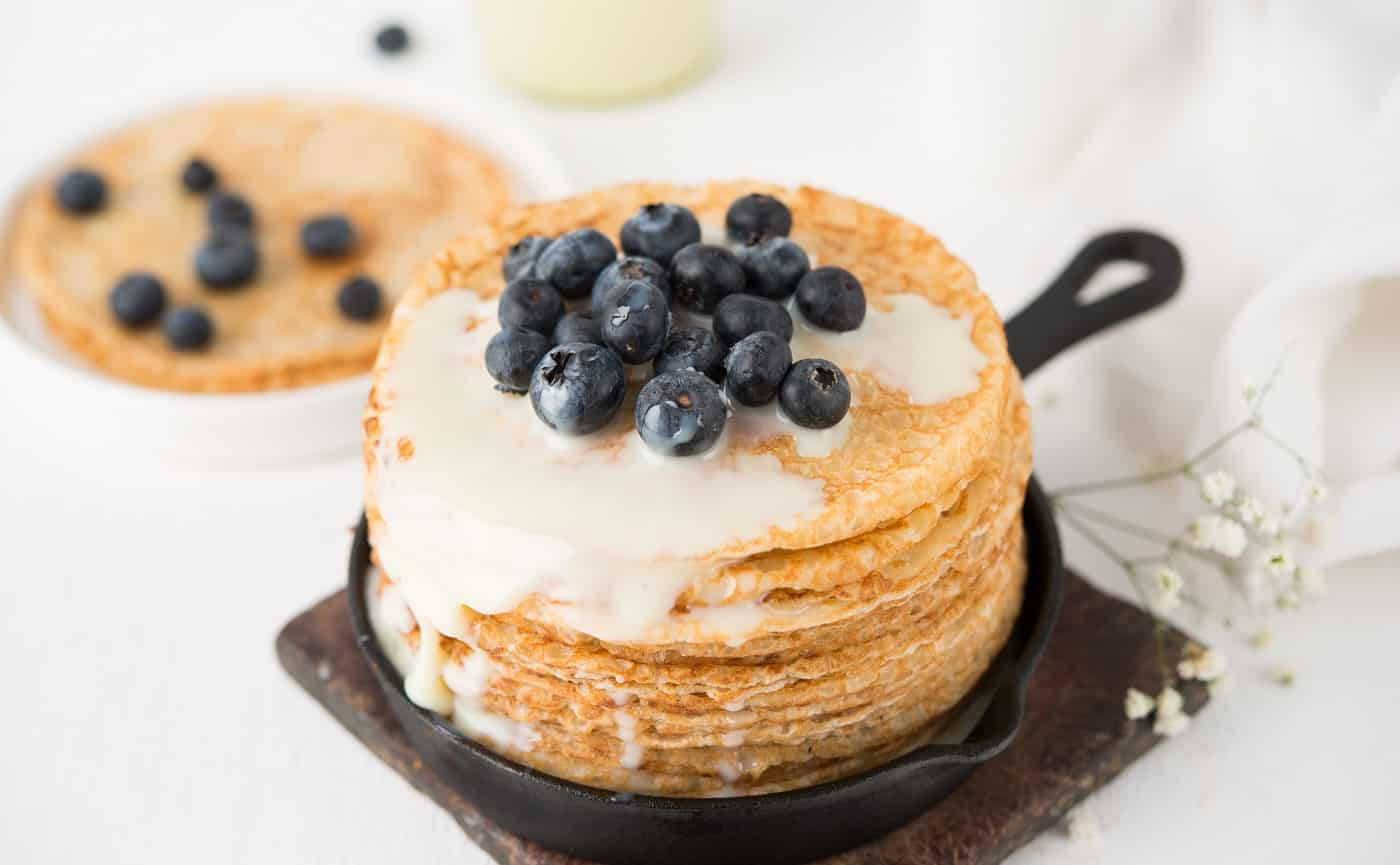 Homemade thin traditional pancakes with condensed milk and blueberries, selective focus, close-up