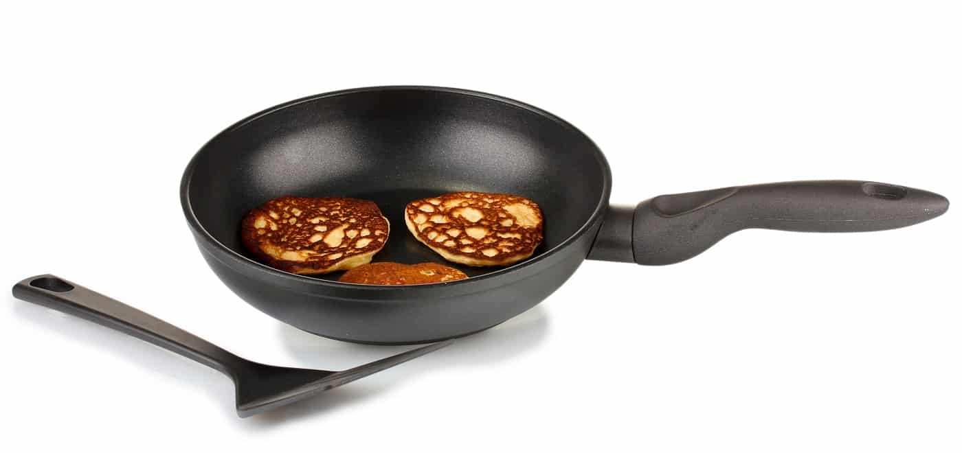 delicious sweet pancakes in frying pan isolated on white