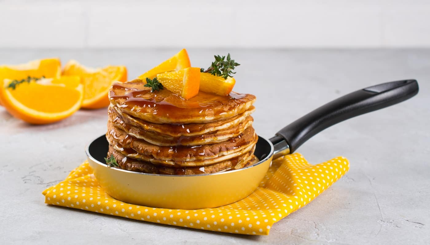 Pancakes with orange and sprinkled maple syrup in a small yellow pan on white background. Breakfast