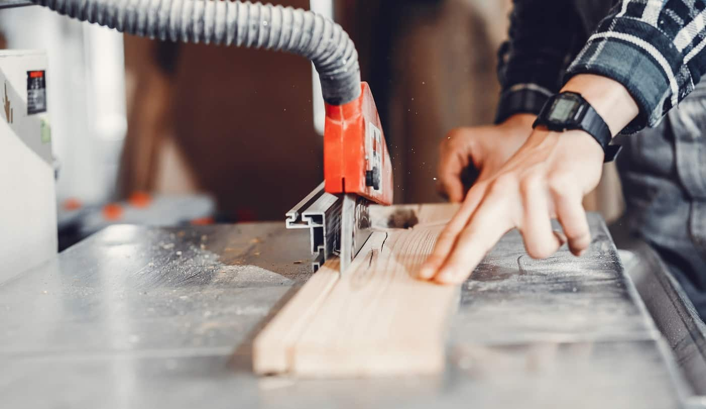 A man carves a tree. The carpenter works in a studio. An engineer provides a tree shape