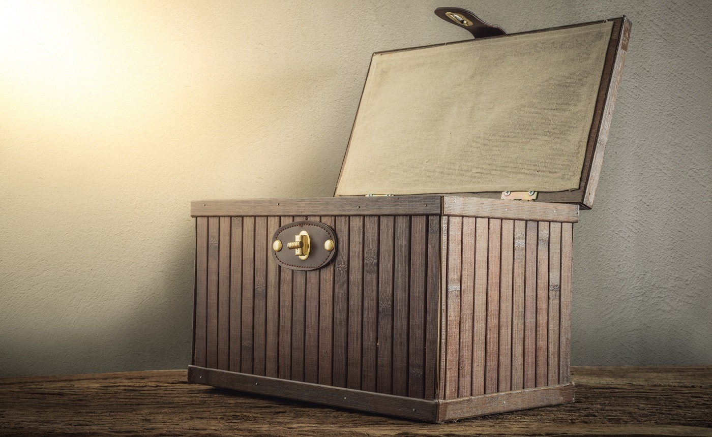 Old wooden chest with open lit on wooden tabletop against grunge wall. vintage tone