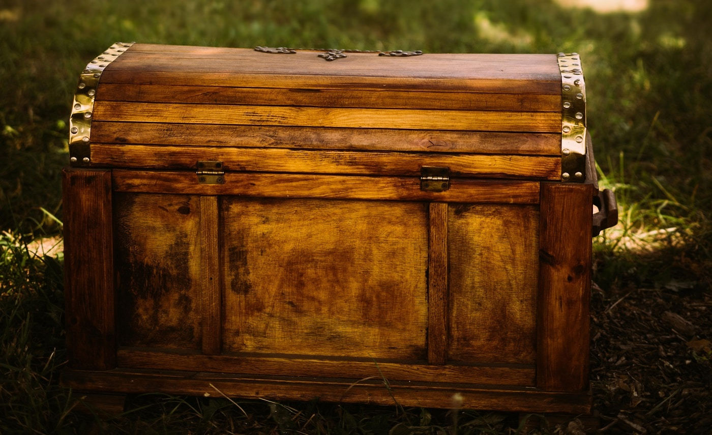 Treasure chest in the foreground and group of people in a background. Warm summer sunny day.