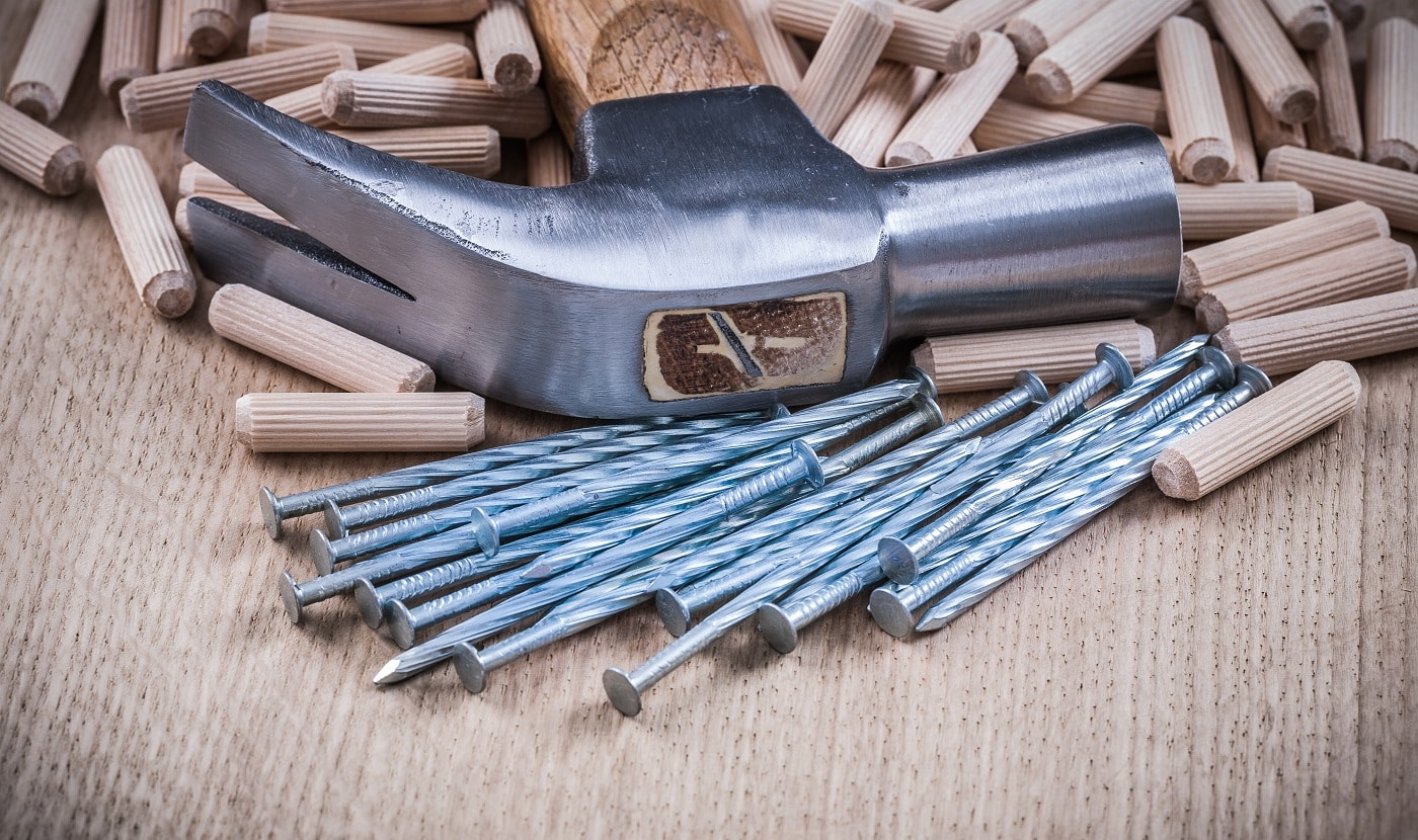 Woodworking dowels nails claw hammer on wooden background.