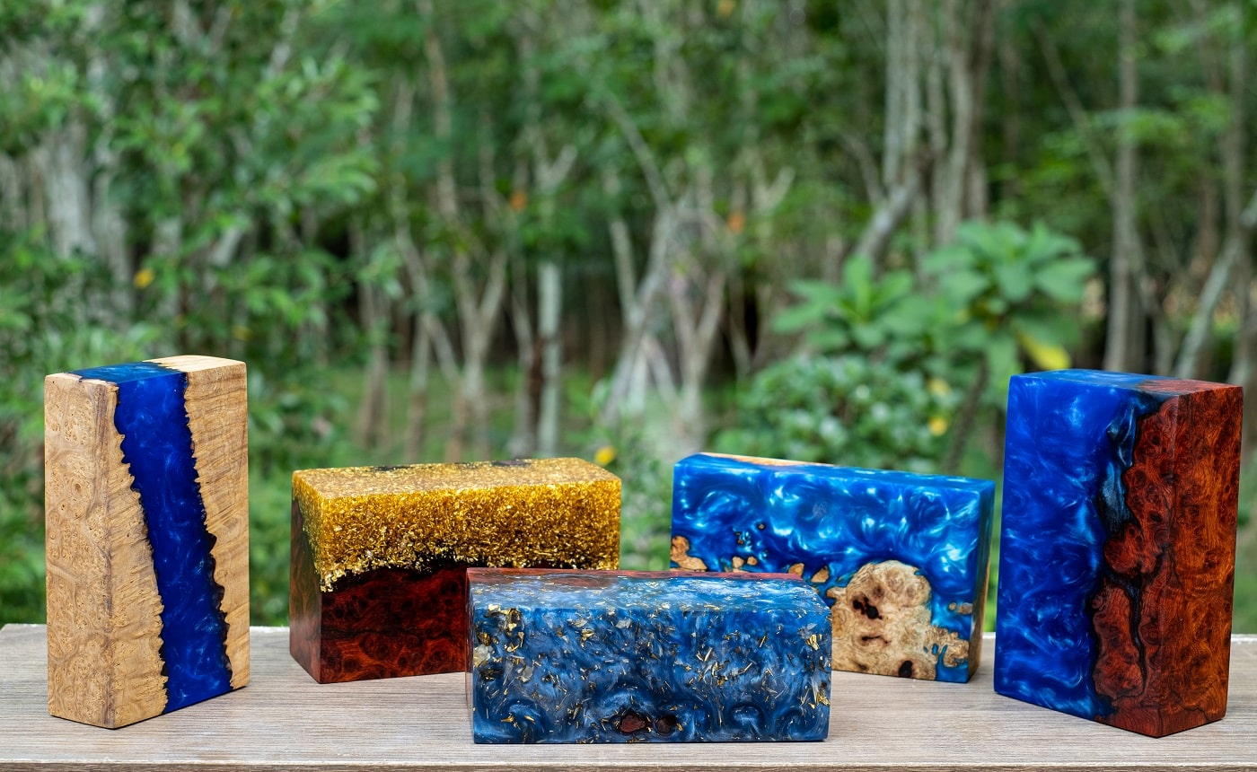 Casting epoxy resin burl wood cube on table at green blured background, Nature wooden