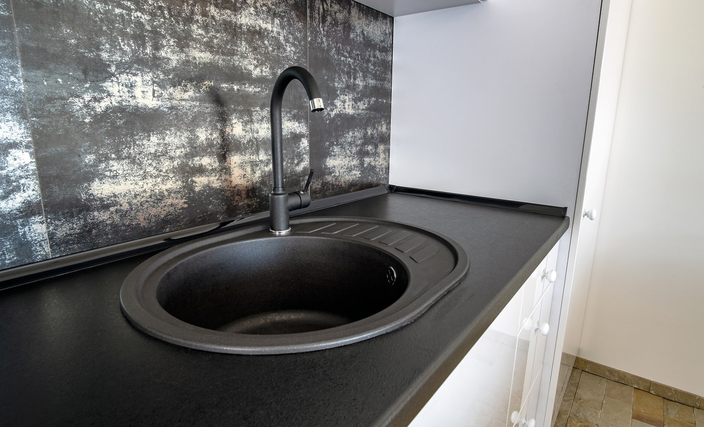 Interior of modern spacious kitchen with white contemporary furniture, black ceramic tiles on the wall and dark granite sink with water tap.