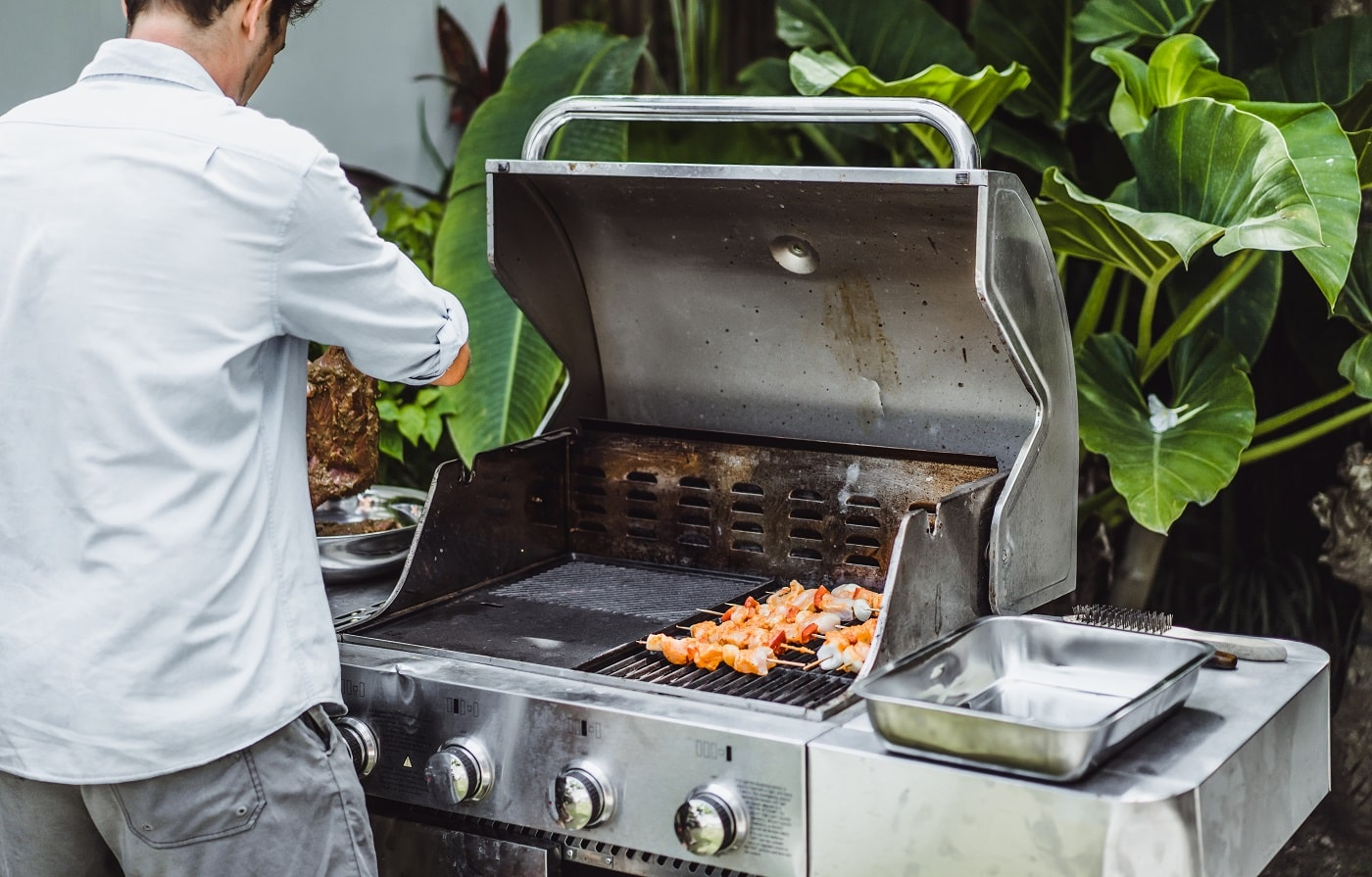 A man in tattoos makes barbecue grill meat outdoors.