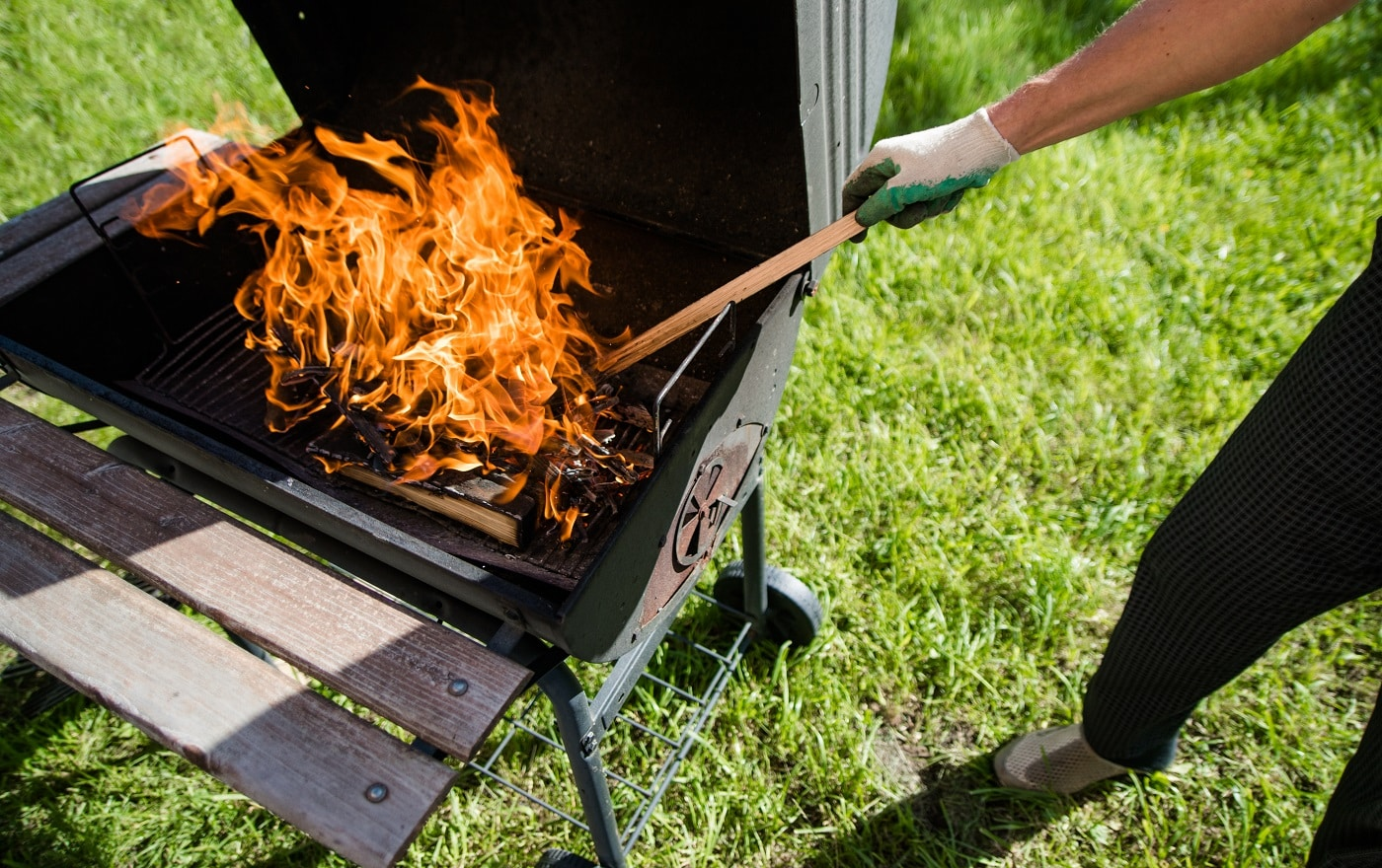 A man in gloves straightens burning wood in the grill. Summer barbecue. General form.