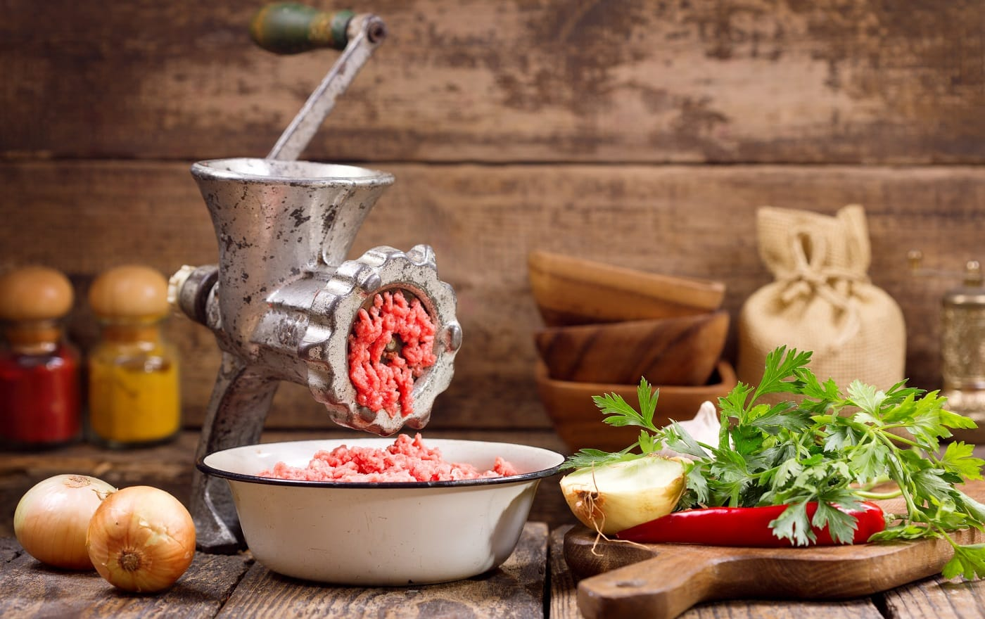 old grinder with minced meat and vegetables on wooden table